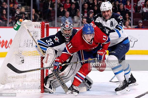 Mark Stuart of the Winnipeg Jets clears Brendan Gallagher of the Montreal Canadiens from in front of goalie Al Montoya of the Winnipeg Jets during...