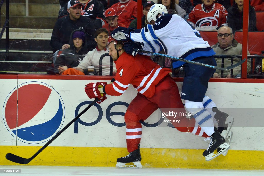 Mark Stuart #5 of the Winnipeg Jets collides with <a gi-track='captionPersonalityLinkClicked' href=/galleries/search?phrase=Andrej+Sekera&family=editorial&specificpeople=722503 ng-click='$event.stopPropagation()'>Andrej Sekera</a> #4 of the Carolina Hurricanes at PNC Arena on February 4, 2013 in Raleigh, North Carolina. The Jets defeated the Hurricanes 2-1.