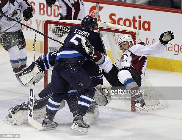 Mark Stuart of the Winnipeg Jets collides with Carl Soderberg of the Colorado Avalanche in first period action in an NHL game at the MTS Centre on...