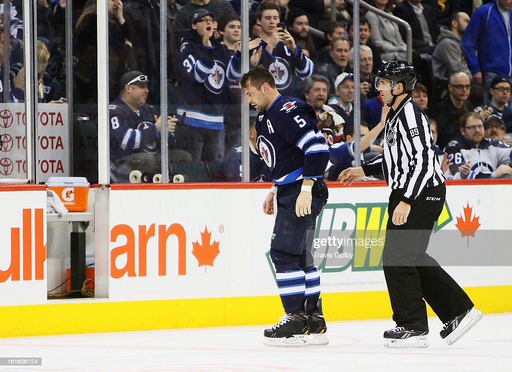 Mark Stuart #5 of the Winnipeg Jets gets escorted to the penalty box by linesman Steve Miller #89 after a second period fight against Tye McGinn #15 of the Philadelphia Flyers (not shown) at the MTS Centre on February 12, 2013 in Winnipeg, Manitoba, Canada.