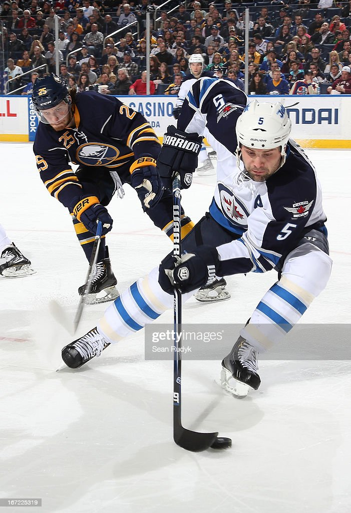 Mark Stuart #5 of the Winnipeg Jets handles the puck against Mikhail Grigorenko #25 of the Buffalo Sabres at First Niagara Center on April 22, 2013 in Buffalo, New York.