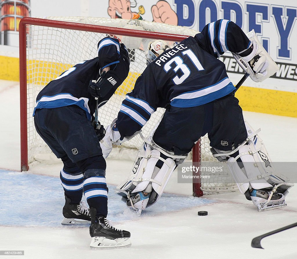 Mark Stuart #5 of the Winnipeg Jets helps out Ondrej Pavelec #31 in third period action in an NHL game against the Pittsburgh Penguins at the MTS Centre on April 3, 2014 in Winnipeg, Manitoba, Canada.