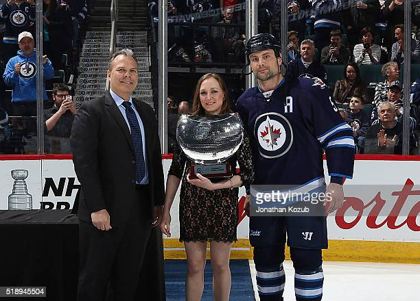Mark Stuart of the Winnipeg Jets is presented with the North West Company Community Service award prior to NHL action against the Minnesota Wild at...