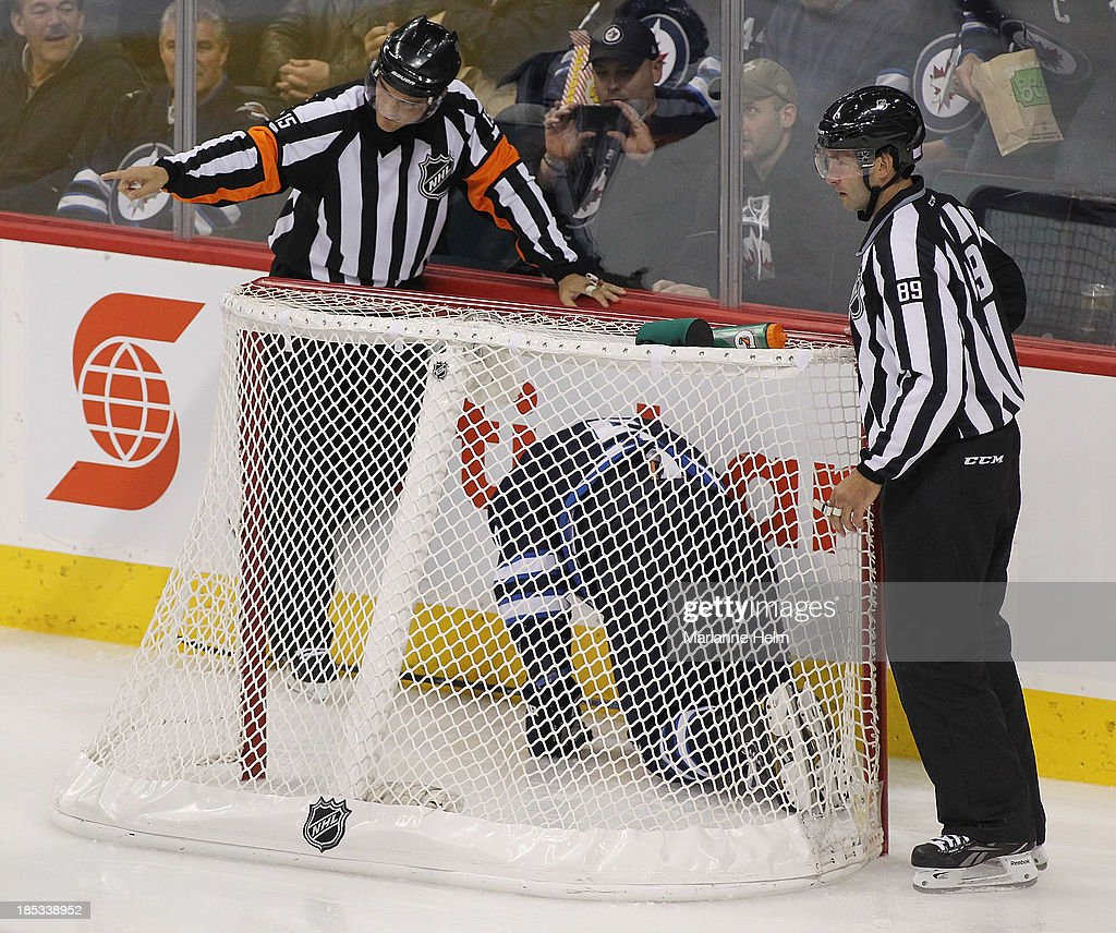 Mark Stuart #5 of the Winnipeg Jets kneels on the ice after crashing into the net as referee Jean Hebert #15 and linesman Steve Miller #89 check on him in thir- period action of an NHL game against the St. Louis Blues at the MTS Centre on October 18, 2013 in Winnipeg, Manitoba, Canada.