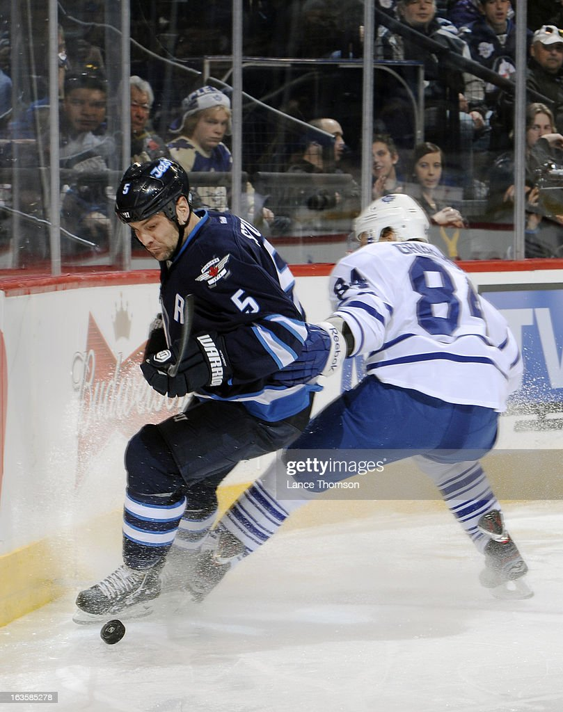 Mark Stuart #5 of the Winnipeg Jets plays the puck away from <a gi-track='captionPersonalityLinkClicked' href=/galleries/search?phrase=Mikhail+Grabovski&family=editorial&specificpeople=2560547 ng-click='$event.stopPropagation()'>Mikhail Grabovski</a> #84 of the Toronto Maple Leafs during third period action at the MTS Centre on March 12, 2013 in Winnipeg, Manitoba, Canada.