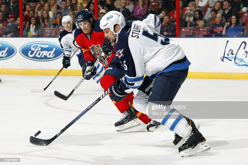 Mark Stuart #5 of the Winnipeg Jets skates with the puck against Jack Skille #12 of the Florida Panthers at the BB&T Center on January 31, 2013 in Sunrise, Florida.