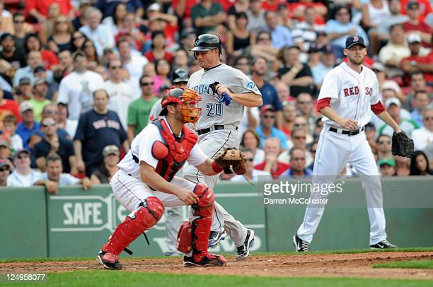 Mark Teahen of the Toronto Blue Jays scores a run in the eighth inning as catcher Jason Varitek of the Boston Red Sox cuts off the throw and pitcher...