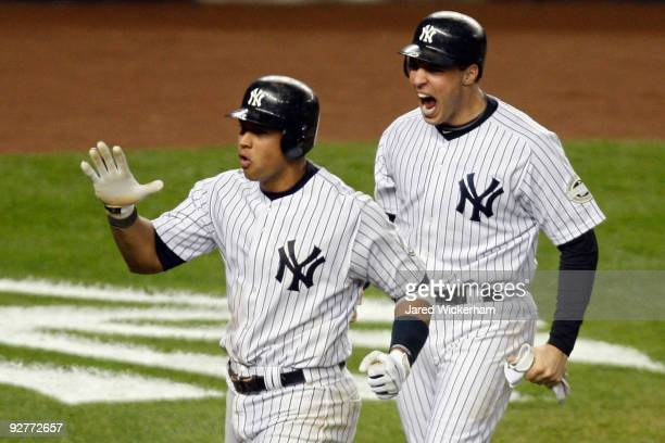 Mark Teixeira and Alex Rodriguez of the New York Yankees celebrate after they scored on a 2run double by Hideki Matsui in the bottom of the fifth...