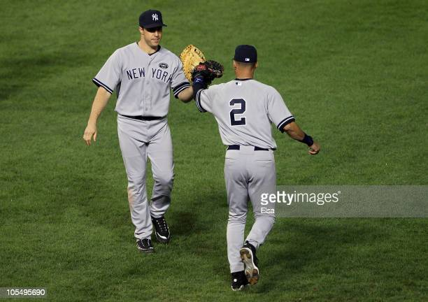Mark Teixeira and Derek Jeter of the New York Yankees celebrate a play against the Texas Rangers in Game One of the ALCS during the 2010 MLB Playoffs...