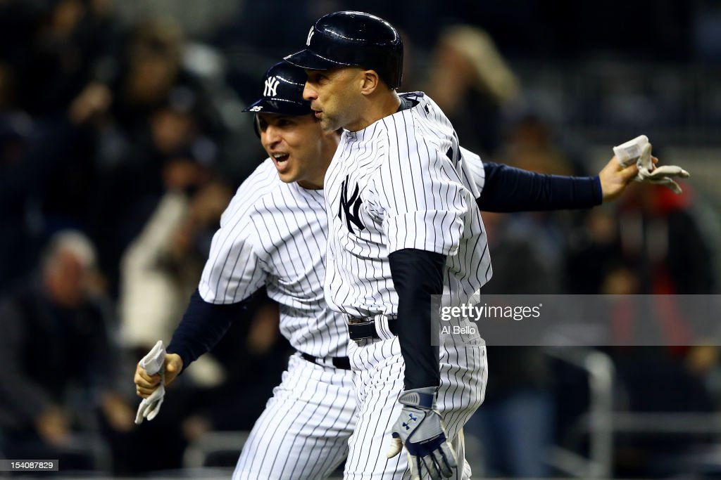 Mark Teixeira #25 and Raul Ibanez #27 of the New York Yankees celebrate after they both scored on a 2-run home run hit by Ibanez in the bottom of the ninth inning against the Detroit Tigers during Game One of the American League Championship Series at Yankee Stadium on October 13, 2012 in the Bronx borough of New York City, New York.