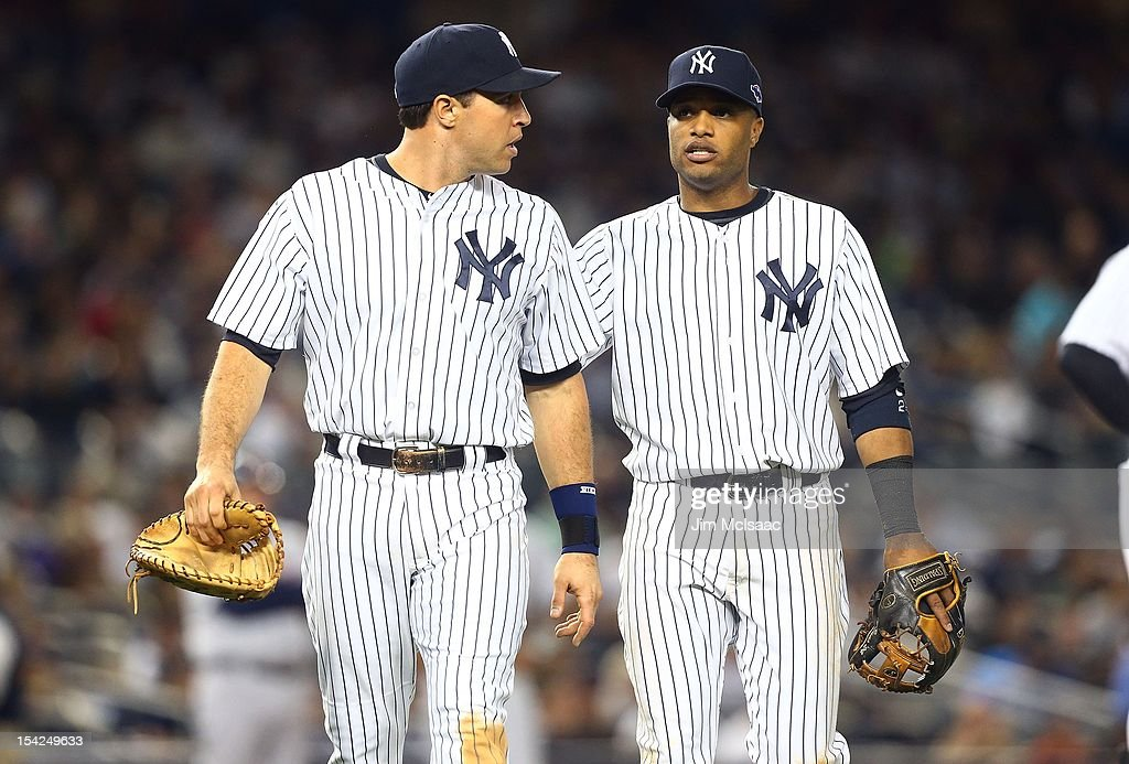Mark Teixeira #25 (L) and Robinson Cano #24 of the New York Yankees look on against the Detroit Tigers during Game Two of the American League Championship Series at Yankee Stadium on October 14, 2012 in the Bronx borough of New York City, New York.. The Tigers defeated the Yankees 3-0.