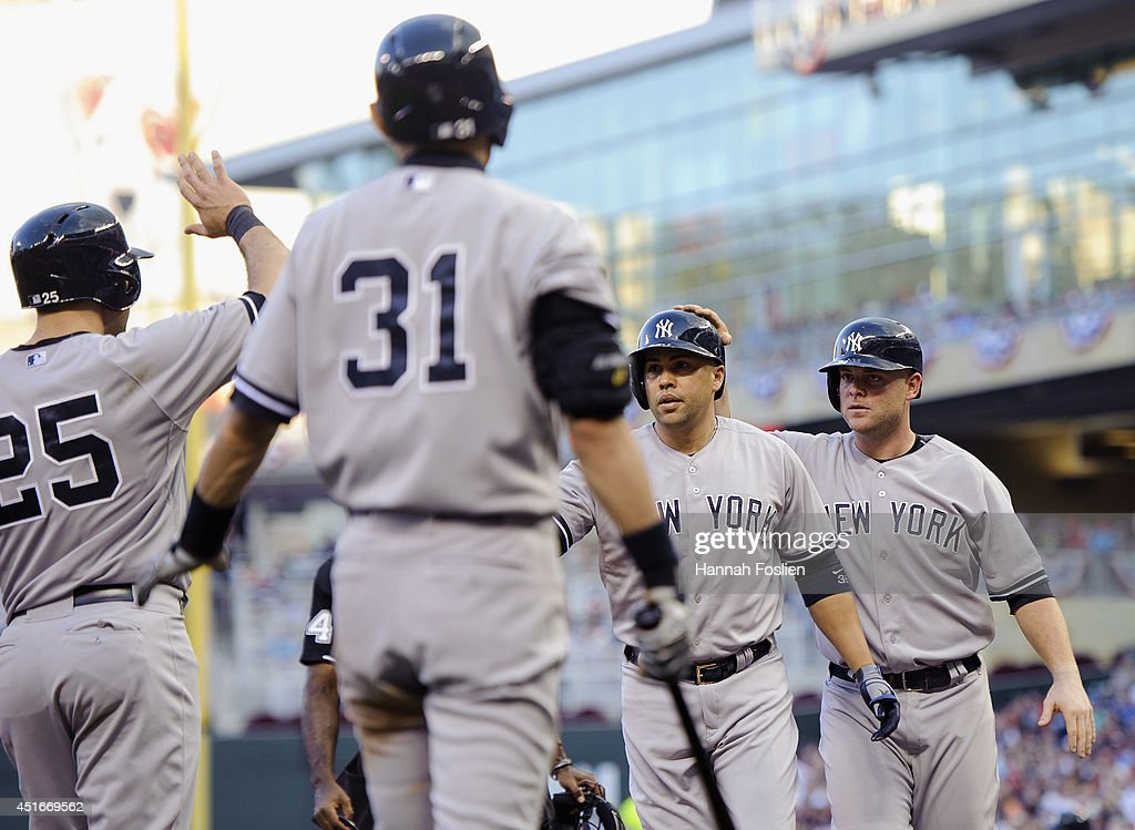Mark Teixeira #25, Ichiro Suzuki #31 and Brian McCann #34 of the New York Yankees congratulate teammate Carlos Beltran #36 on a three-run home run against the Minnesota Twins during the fifth inning of the game on July 3, 2014 at Target Field in Minneapolis, Minnesota. The Yankees defeated the Twins 7-4.