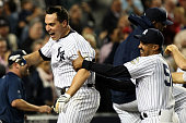 Mark Teixeira of the New York Yankees celebrates with Tony Pena aftering hitting a walk off home run in the eleventh inning against the Minnesota...