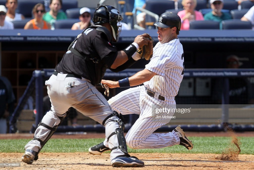 Mark Teixeira #25 of the New York Yankees is tagged out trying to score on a sacrifice fly in the fifth inning by Jose Molina #8 of the Toronto Blue Jays on July 4, 2010 at Yankee Stadium in the Bronx borough of New York City.