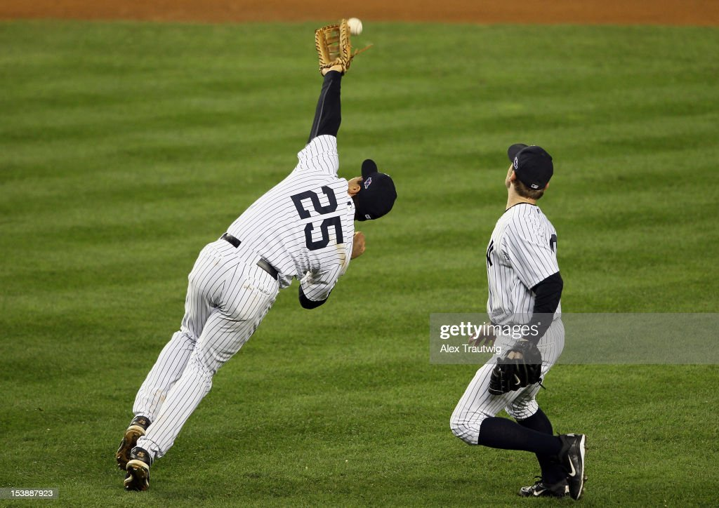 Mark Teixeira #25 of the New York Yankees miscommunicates with David Robertson #30 and misses a catch in the top of the twelfth inning during Game Three of the American League Division Series against the Baltimore Orioles at Yankee Stadium on October 10, 2012 in the Bronx borough of New York City.