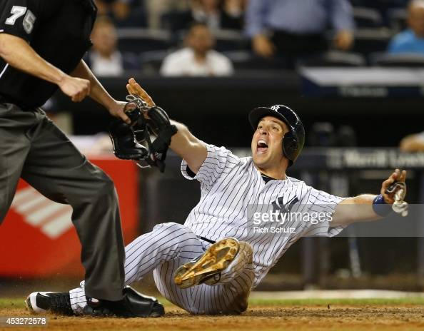 Mark Teixeira of the New York Yankees reacts after being called out by home plate umpire Tom Woodring the play was reversed on video review as the...