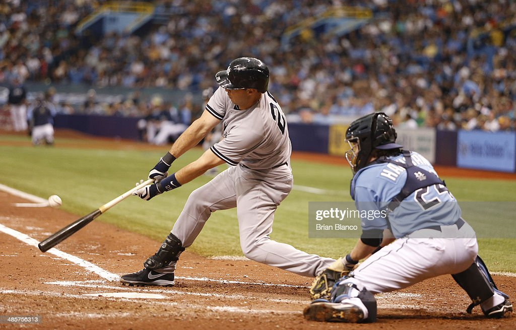 <a gi-track='captionPersonalityLinkClicked' href=/galleries/search?phrase=Mark+Teixeira&family=editorial&specificpeople=209239 ng-click='$event.stopPropagation()'>Mark Teixeira</a> #25 of the New York Yankees singles to right field in front of catcher <a gi-track='captionPersonalityLinkClicked' href=/galleries/search?phrase=Ryan+Hanigan&family=editorial&specificpeople=833982 ng-click='$event.stopPropagation()'>Ryan Hanigan</a> #24 of the Tampa Bay Rays during the sixth inning of a game on April 20, 2014 at Tropicana Field in St. Petersburg, Florida.