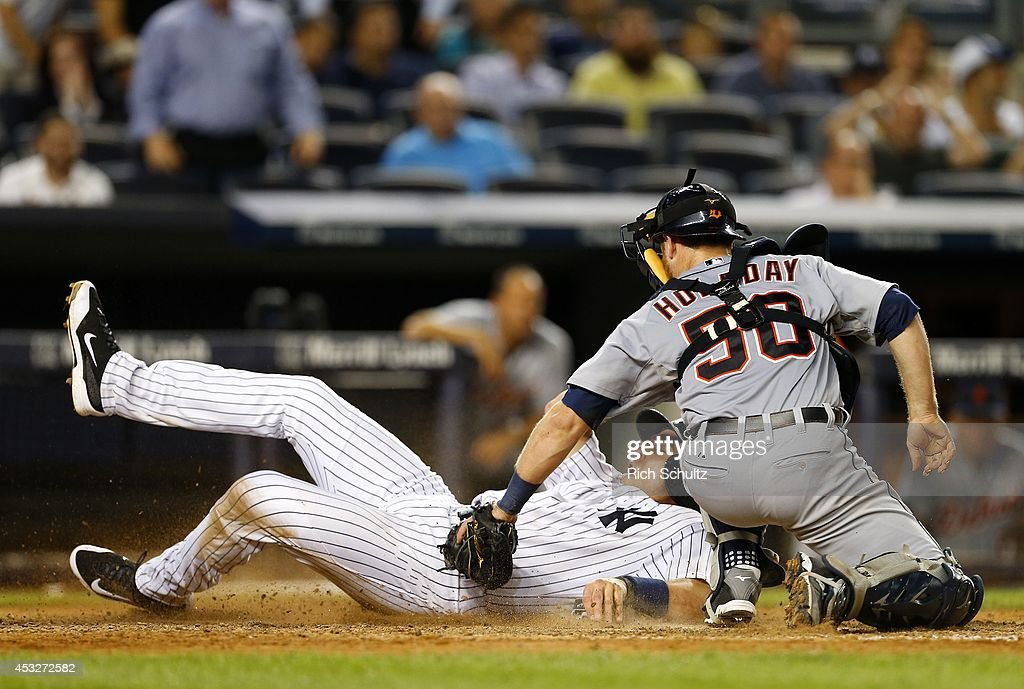 Mark Teixeira #25 of the New York Yankees slides safely into home as before the tag by catcher Bryan Holaday #50 of the Detroit Tigers on a fielders choice hit by Brian McCann #34 during the eighth inning of a MLB baseball game at Yankee Stadium on August 6, 2014 in the Bronx borough of New York City. The Yankees defeated the Tigers 5-1.