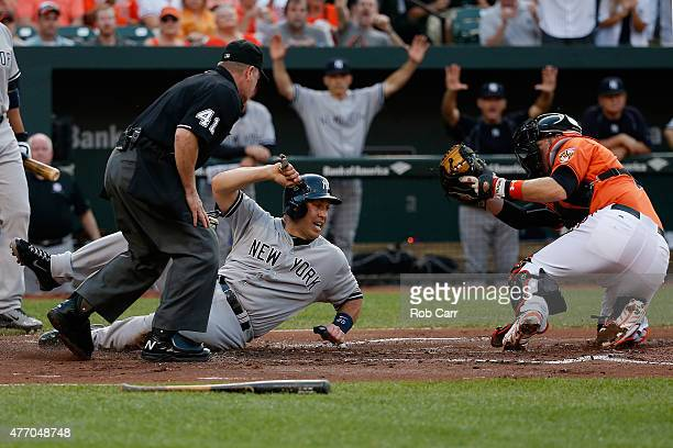 Mark Teixeira of the New York Yankees slides safely into home plate to score a run as catcher Matt Wieters of the Baltimore Orioles applies the tag...