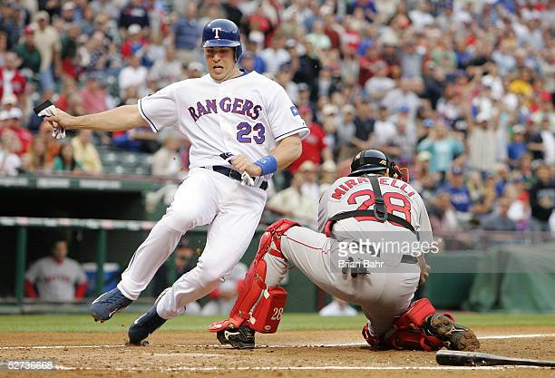 Mark Teixeira of the Texas Rangers avoids catcher Doug Mirabelli of the Boston Red Sox to score in the first inning at Ameriquest Field at Arlington...