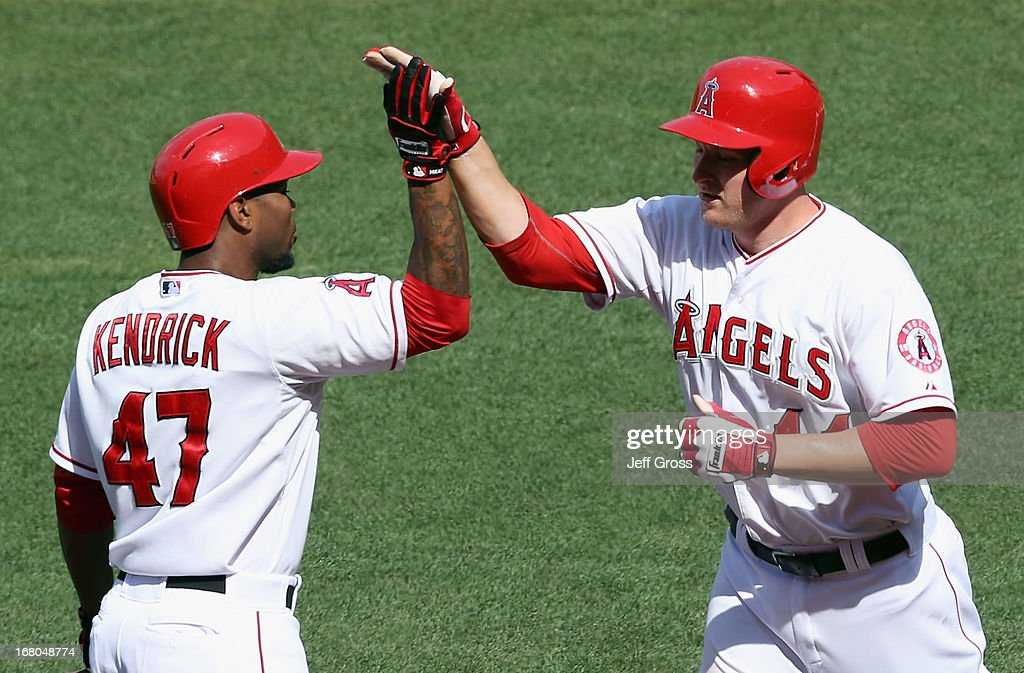 <a gi-track='captionPersonalityLinkClicked' href=/galleries/search?phrase=Mark+Trumbo&family=editorial&specificpeople=4921667 ng-click='$event.stopPropagation()'>Mark Trumbo</a> (R) #44 of the Los Angeles Angels of Anaheim is congratulated by <a gi-track='captionPersonalityLinkClicked' href=/galleries/search?phrase=Howie+Kendrick&family=editorial&specificpeople=628938 ng-click='$event.stopPropagation()'>Howie Kendrick</a> #47 after hitting a two-run home run in the seventh inning against the Baltimore Orioles at Angel Stadium of Anaheim on May 4, 2013 in Anaheim, California. The Orioles defeated the Angels 5-4 in ten innings.