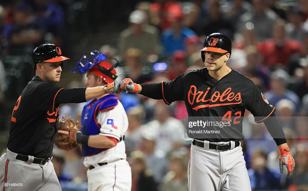 <a gi-track='captionPersonalityLinkClicked' href=/galleries/search?phrase=Mark+Trumbo&family=editorial&specificpeople=4921667 ng-click='$event.stopPropagation()'>Mark Trumbo</a> celebrates a homerun with <a gi-track='captionPersonalityLinkClicked' href=/galleries/search?phrase=Chris+Davis+-+Baseball+-+Texas+Rangers&family=editorial&specificpeople=7129264 ng-click='$event.stopPropagation()'>Chris Davis</a> of the Baltimore Orioles against the Texas Rangers in the seventh inning at Globe Life Park in Arlington on April 15, 2016 in Arlington, Texas. All players are wearing #42 in honor of Jackie Robinson Day.