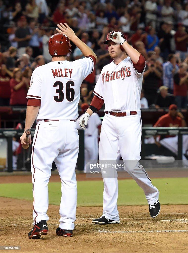 Mark Trumbo of the Arizona Diamondbacks and teammate Wade Miley celebrate a third inning grand slam against the San Francisco Giants at Chase Field...