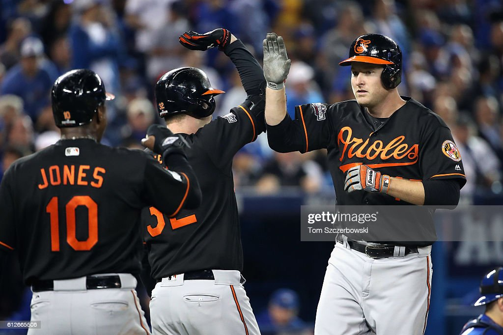 Mark Trumbo #45 of the Baltimore Orioles (R) celebrates with Adam Jones #10 after hitting a two-run home run in the fourth inning against the Toronto Blue Jays during the American League Wild Card game at Rogers Centre on October 4, 2016 in Toronto, Canada.