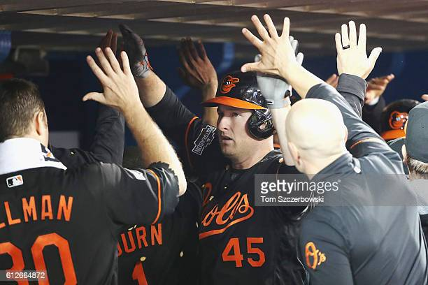 Mark Trumbo of the Baltimore Orioles celebrates with teammates in the dugout after hitting a tworun home run in the fourth inning against the Toronto...