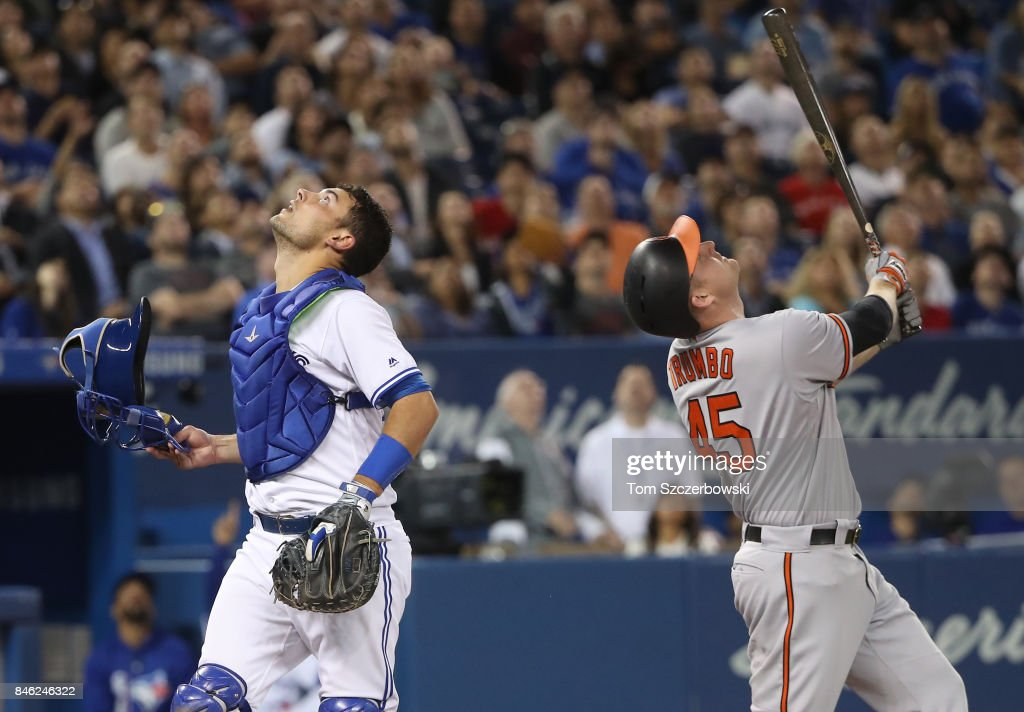 Mark Trumbo #45 of the Baltimore Orioles looks up as he pops out in foul territory in the fifth inning during MLB game action as Luke Maile #22 of the Toronto Blue Jays tracks the baseball before catching it at Rogers Centre on September 12, 2017 in Toronto, Canada.