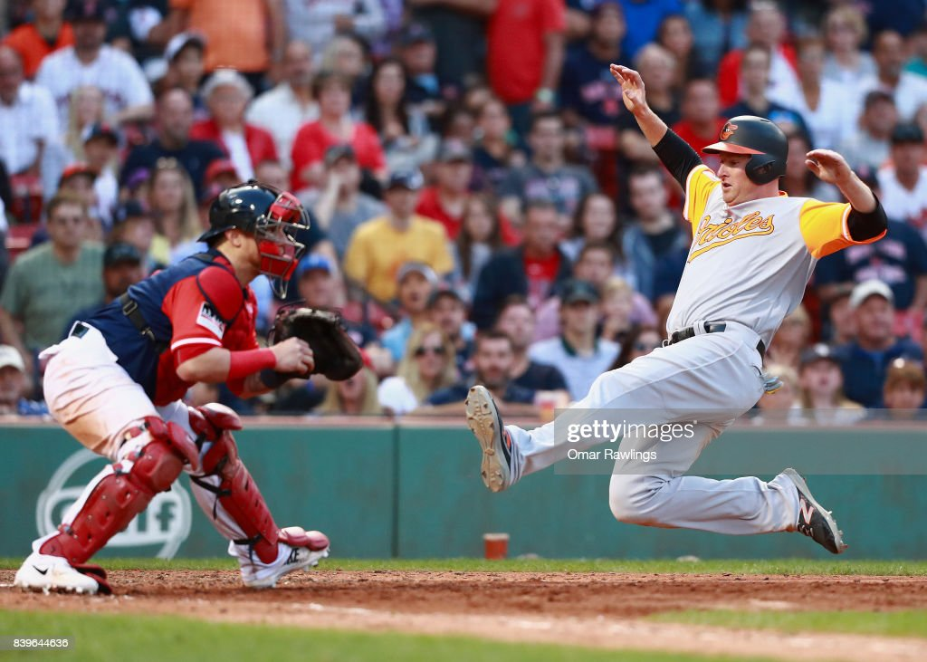 Mark Trumbo #45 of the Baltimore Orioles slides into homeplate at the top of the ninth inning during the game against the Boston Red Sox at Fenway Park on August 26, 2017 in Boston, Massachusetts.