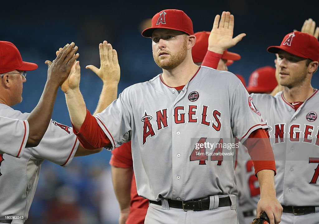 <a gi-track='captionPersonalityLinkClicked' href=/galleries/search?phrase=Mark+Trumbo&family=editorial&specificpeople=4921667 ng-click='$event.stopPropagation()'>Mark Trumbo</a> #44 of the Los Angeles Angels of Anaheim celebrates a victory with teammates during MLB game action against the Toronto Blue Jays on September 10, 2013 at Rogers Centre in Toronto, Ontario, Canada.