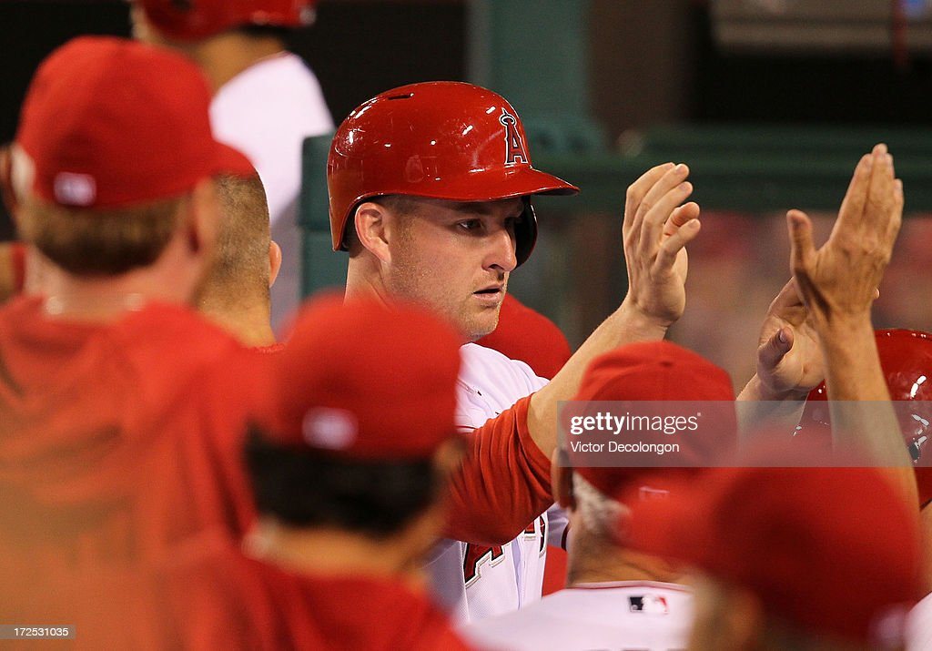 <a gi-track='captionPersonalityLinkClicked' href=/galleries/search?phrase=Mark+Trumbo&family=editorial&specificpeople=4921667 ng-click='$event.stopPropagation()'>Mark Trumbo</a> #44 of the Los Angeles Angels of Anaheim celebrates in the dugout with teammates after scoring on a single to center by Alberto Callaspo #6 (not in photo) in the seventh inning during the MLB game against the Pittsburgh Pirates at Angel Stadium of Anaheim on June 21, 2013 in Anaheim, California. The Pirates defeated the Angels 5-2.