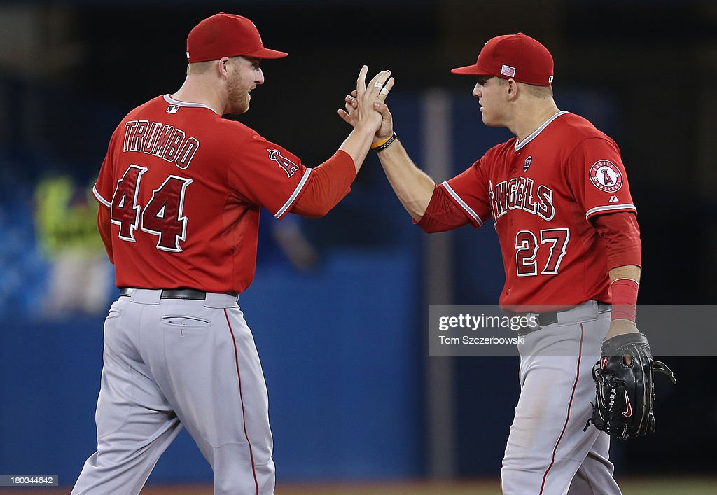 <a gi-track='captionPersonalityLinkClicked' href=/galleries/search?phrase=Mark+Trumbo&family=editorial&specificpeople=4921667 ng-click='$event.stopPropagation()'>Mark Trumbo</a> #44 of the Los Angeles Angels of Anaheim celebrates their victory with <a gi-track='captionPersonalityLinkClicked' href=/galleries/search?phrase=Mike+Trout&family=editorial&specificpeople=7091306 ng-click='$event.stopPropagation()'>Mike Trout</a> #27 during MLB game action against the Toronto Blue Jays on September 11, 2013 at Rogers Centre in Toronto, Ontario, Canada.