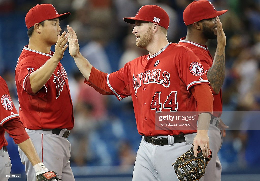 <a gi-track='captionPersonalityLinkClicked' href=/galleries/search?phrase=Mark+Trumbo&family=editorial&specificpeople=4921667 ng-click='$event.stopPropagation()'>Mark Trumbo</a> #44 of the Los Angeles Angels of Anaheim celebrates their victory with <a gi-track='captionPersonalityLinkClicked' href=/galleries/search?phrase=Hank+Conger&family=editorial&specificpeople=713039 ng-click='$event.stopPropagation()'>Hank Conger</a> #16 during MLB game action against the Toronto Blue Jays on September 11, 2013 at Rogers Centre in Toronto, Ontario, Canada.