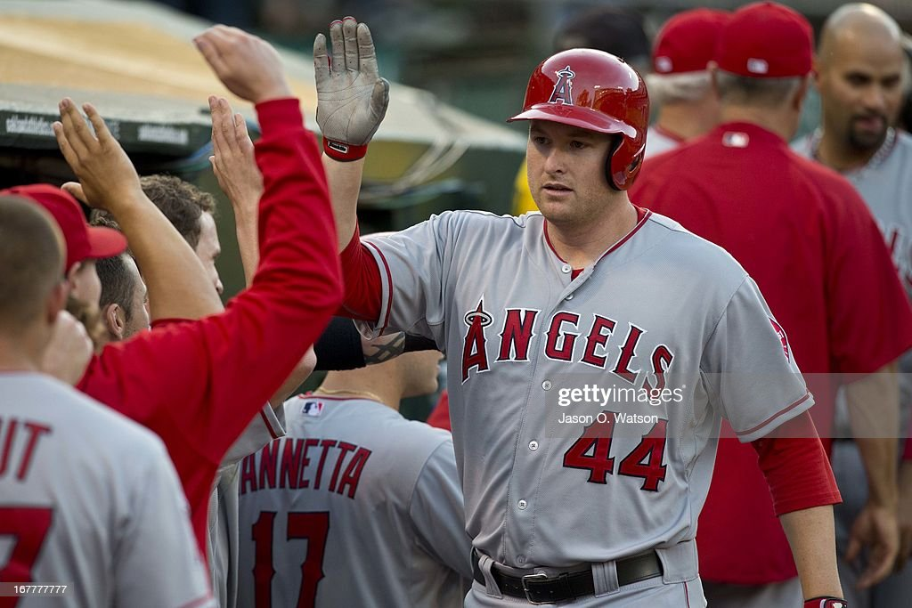 Mark Trumbo #44 of the Los Angeles Angels of Anaheim is congratulated by teammates in the dugout after hitting a home run against the Oakland Athletics during the second inning at O.co Coliseum on April 29, 2013 in Oakland, California.