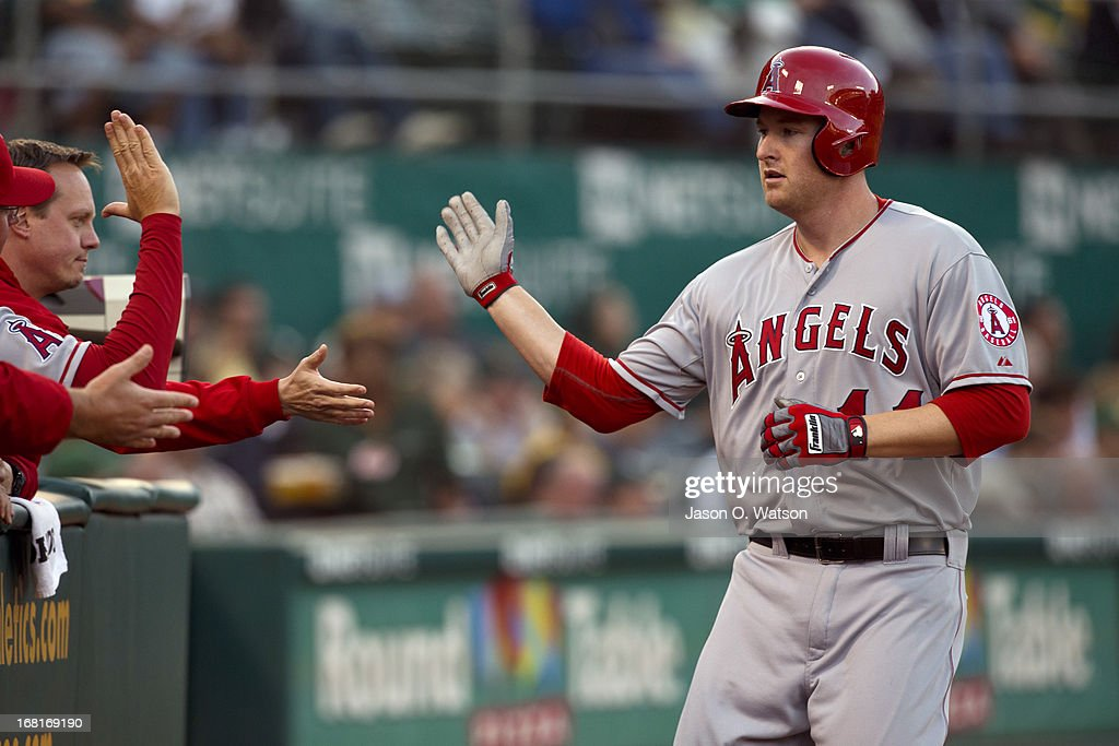 Mark Trumbo #44 of the Los Angeles Angels of Anaheim is congratulated by teammates in the dugout after hitting a home run against the Oakland Athletics during the second inning at O.co Coliseum on April 29, 2013 in Oakland, California. The Oakland Athletics defeated the Los Angeles Angels of Anaheim 10-8 in 19 innings.