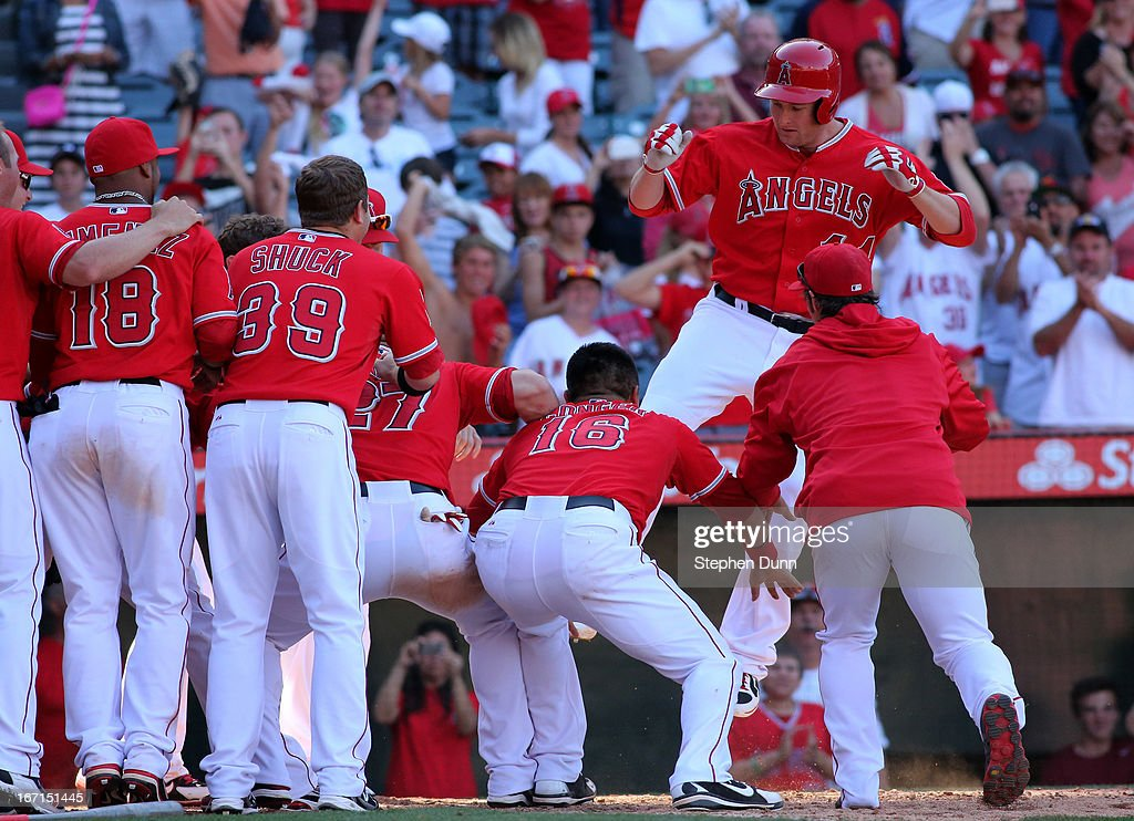 <a gi-track='captionPersonalityLinkClicked' href=/galleries/search?phrase=Mark+Trumbo&family=editorial&specificpeople=4921667 ng-click='$event.stopPropagation()'>Mark Trumbo</a> #44 (R) of the Los Angeles Angels of Anaheim is greeted by teammates as he jumps on home plate after hitting a game winning walk off home run in the 13th inning against the Detroit Tigers at Angel Stadium of Anaheim on April 21, 2013 in Anaheim, California. The Angels won 4-3 in 13 innings.
