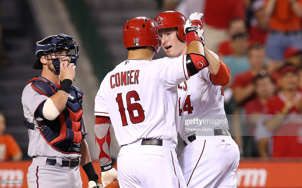 <a gi-track='captionPersonalityLinkClicked' href=/galleries/search?phrase=Mark+Trumbo&family=editorial&specificpeople=4921667 ng-click='$event.stopPropagation()'>Mark Trumbo</a> #4 of the Los Angeles Angels of Anaheim is greeted by <a gi-track='captionPersonalityLinkClicked' href=/galleries/search?phrase=Hank+Conger&family=editorial&specificpeople=713039 ng-click='$event.stopPropagation()'>Hank Conger</a> #16 after hitting a solo home run in the fourth inning as catcher <a gi-track='captionPersonalityLinkClicked' href=/galleries/search?phrase=Chris+Herrmann&family=editorial&specificpeople=7553012 ng-click='$event.stopPropagation()'>Chris Herrmann</a> #12 of the Minnesota Twins looks on at Angel Stadium of Anaheim on July 23, 2013 in Anaheim, California.