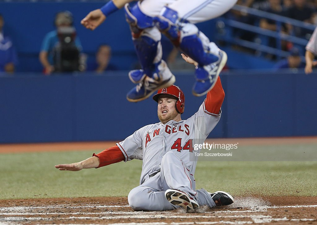 <a gi-track='captionPersonalityLinkClicked' href=/galleries/search?phrase=Mark+Trumbo&family=editorial&specificpeople=4921667 ng-click='$event.stopPropagation()'>Mark Trumbo</a> #44 of the Los Angeles Angels of Anaheim scores a run in the third inning during MLB game action as <a gi-track='captionPersonalityLinkClicked' href=/galleries/search?phrase=J.P.+Arencibia&family=editorial&specificpeople=4959430 ng-click='$event.stopPropagation()'>J.P. Arencibia</a> #9 of the Toronto Blue Jays jumps for the high throw to home plate on September 10, 2013 at Rogers Centre in Toronto, Ontario, Canada.