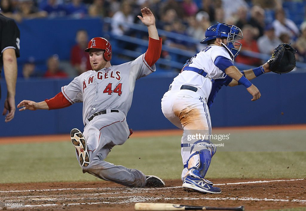 <a gi-track='captionPersonalityLinkClicked' href=/galleries/search?phrase=Mark+Trumbo&family=editorial&specificpeople=4921667 ng-click='$event.stopPropagation()'>Mark Trumbo</a> #44 of the Los Angeles Angels of Anaheim slides into home plate to score a run in the eighth inning during MLB game action as <a gi-track='captionPersonalityLinkClicked' href=/galleries/search?phrase=J.P.+Arencibia&family=editorial&specificpeople=4959430 ng-click='$event.stopPropagation()'>J.P. Arencibia</a> #9 of the Toronto Blue Jays waits for the throw on September 10, 2013 at Rogers Centre in Toronto, Ontario, Canada.