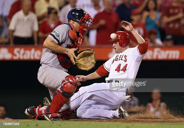 Mark Trumbo of the Los Angeles Angels of Anaheim slides safely into home and scores a run past catcher Ryan Lavarnway of the Boston Red Sox in the...