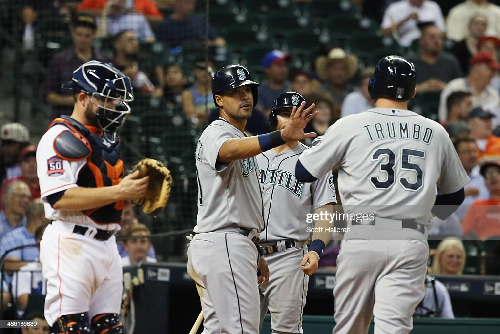 Mark Trumbo of the Seattle Mariners is greeted by Franklin Gutierrez after Trumbo hit a tworun home run in the fifth inning off Vincent Velasquez of...