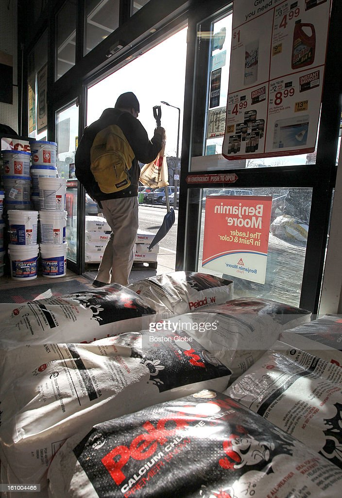 Mark Umstot of Boston, who purchased a shovel to prepare for the upcoming storm, walks by piles of ice melt on his way out of the Model Hardware store.
