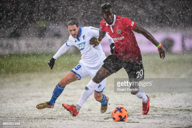 Mark Uth of 1899 Hoffenheim and Salif Sane of Hannover 96 battle for the ball during a heavy snow storm during the Bundesliga match between Hannover...