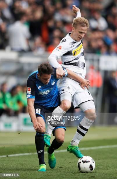 Mark Uth of 1899 Hoffenheim is challenged by Oscar Wendt of Borussia Moenchengladbach during the Bundesliga match between TSG 1899 Hoffenheim and...