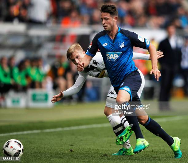 Mark Uth of 1899 Hoffenheim is challenged by Oscar Wendt of Borussia Moenchengladbach during the Bundesliga match between TSG 1899 Hoffenheim and...