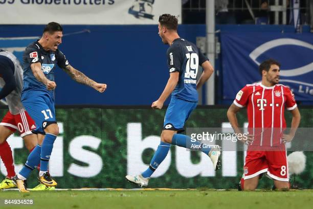 Mark Uth of Hoffenheim celebrates his goal with Steven Zuber of Hoffenheim while Javi Martinez of Bayern Muenchen kneels on the pitch during the...