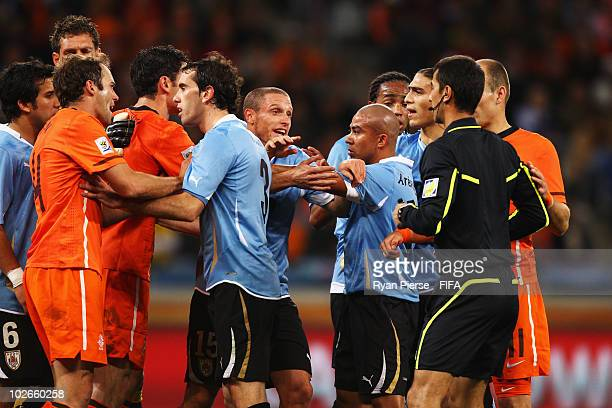 Mark Van Bommel and Joris Mathijsen of the Netherlands protest to Uruguay players and Referee Ravshan Irmatov after Martin Caceres of Uruguay's...