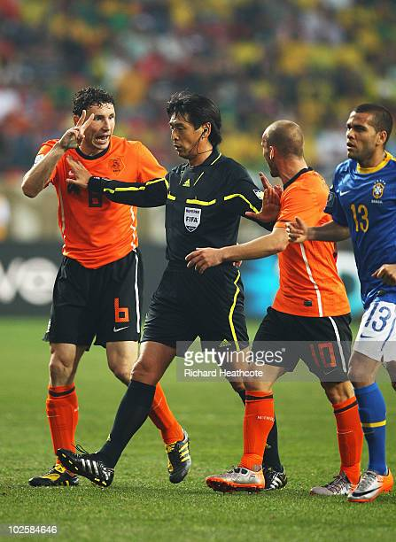 Mark Van Bommel and Wesley Sneijder of the Netherlands speak with referee Yuichi Nishimura during the 2010 FIFA World Cup South Africa Quarter Final...